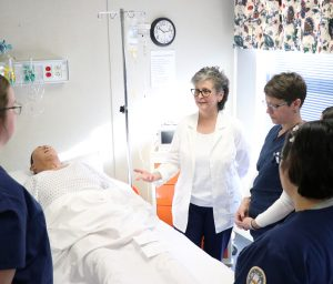 Dr. Maiocco demonstrates patient care techniques to AB nursing students during a simulation lab experience.